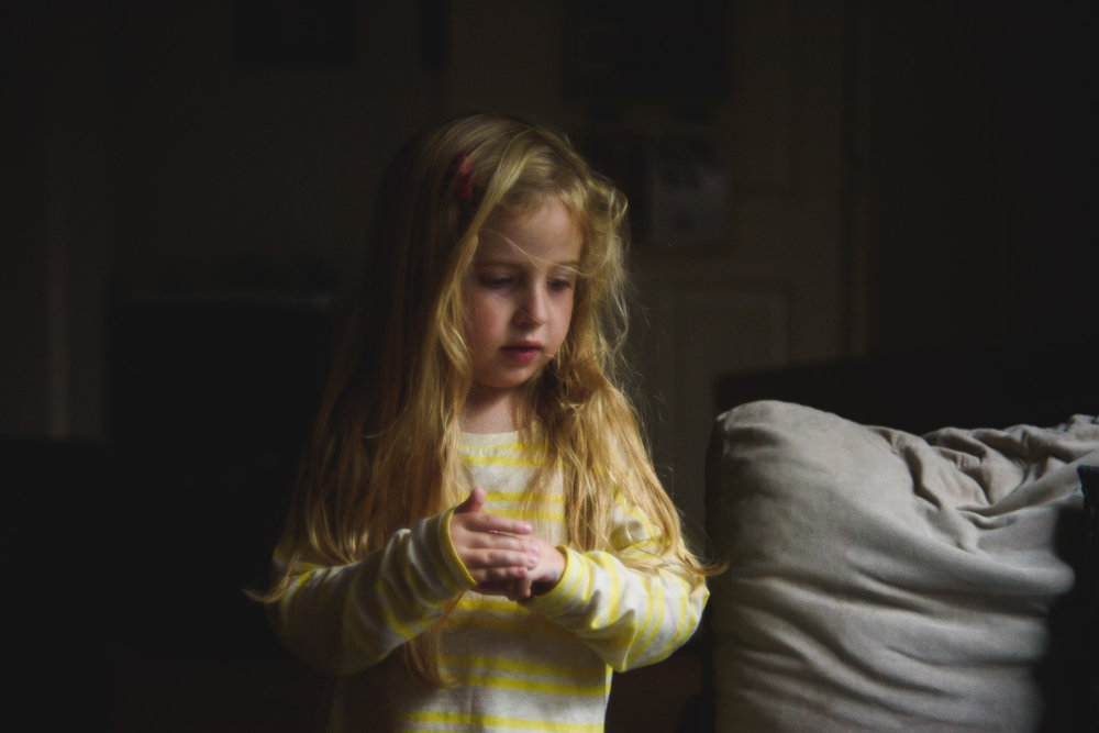 Little girl in a shadowy living room.