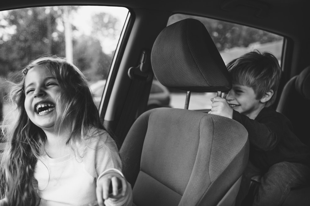 Kids laughing in parked car.