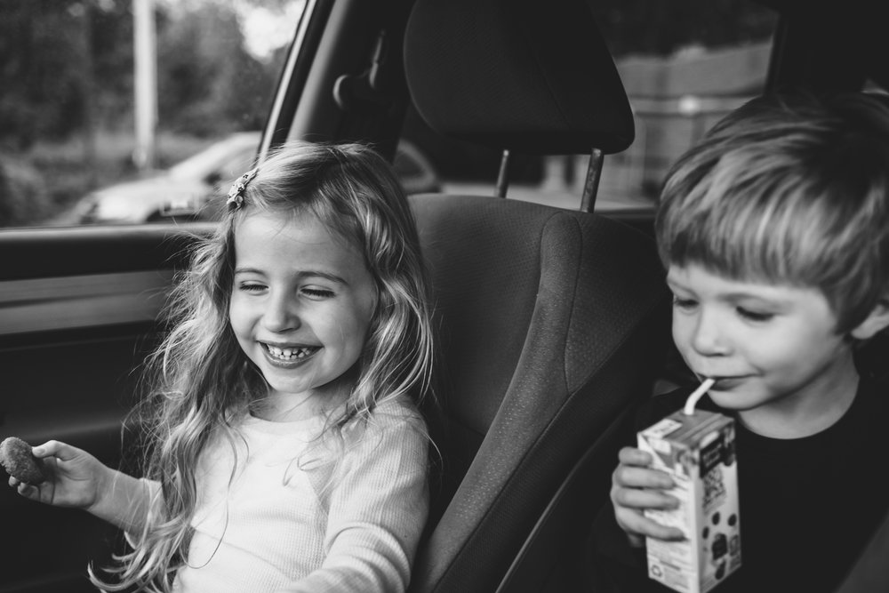 Brother and sister eating in parked car.