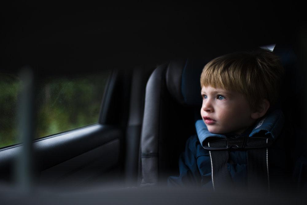 Little boy looking out of car window.