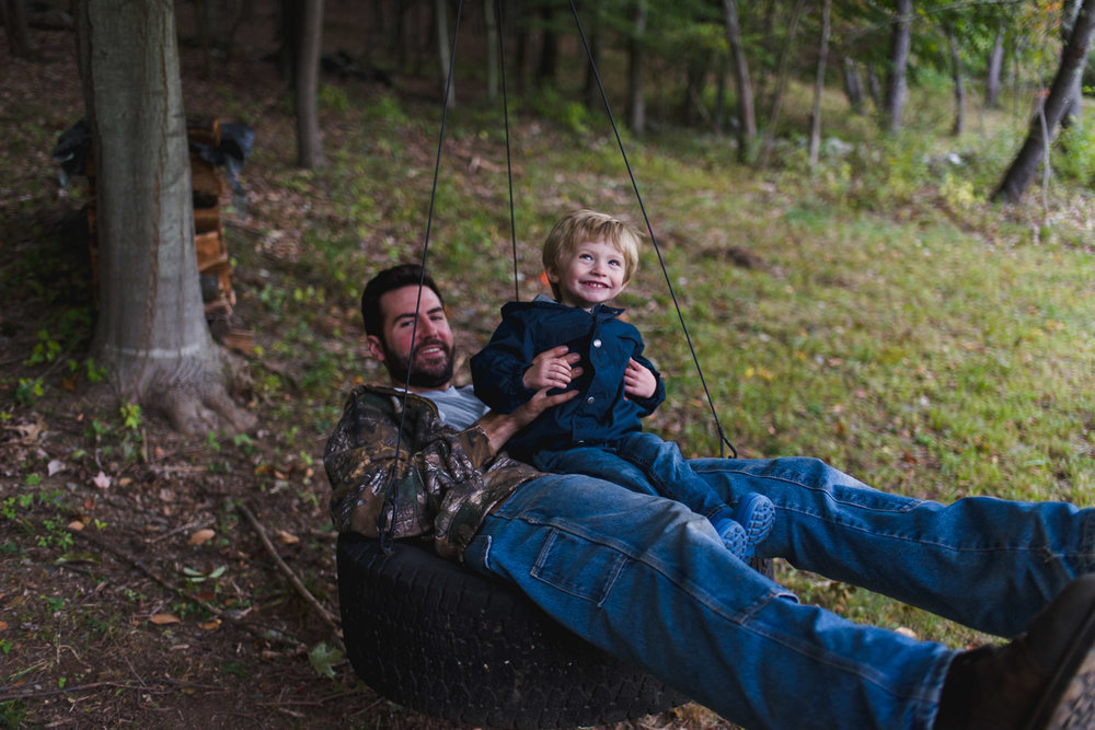 Toddler boy on tire swing with Dad.