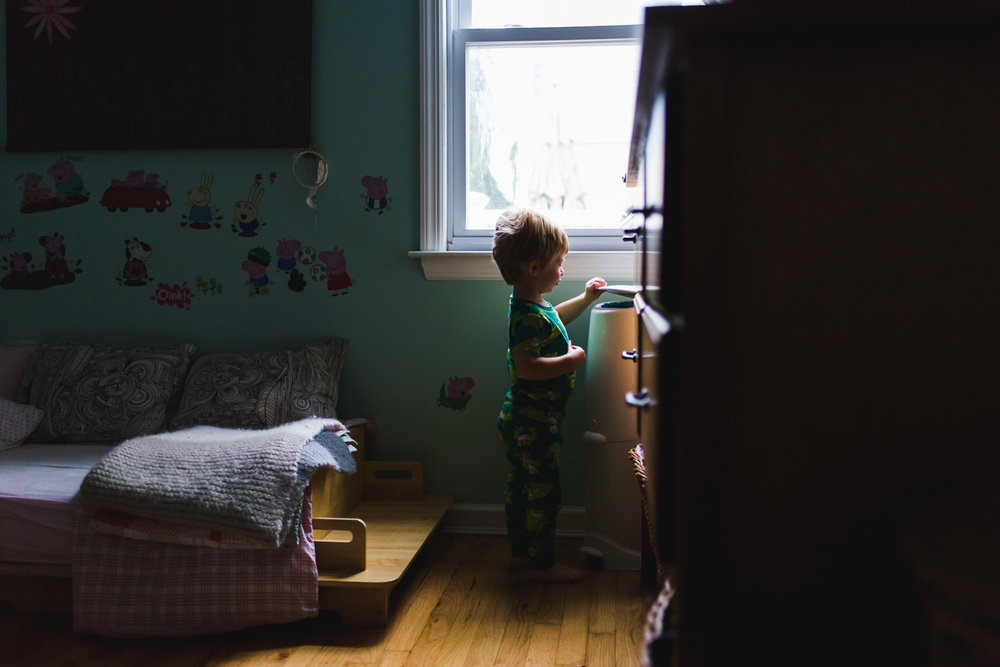 Little boy putting garbage in diaper genie.