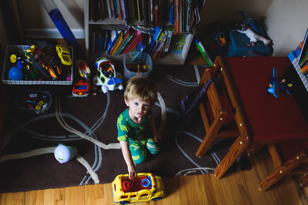 Little boy playing with toys in the living room.