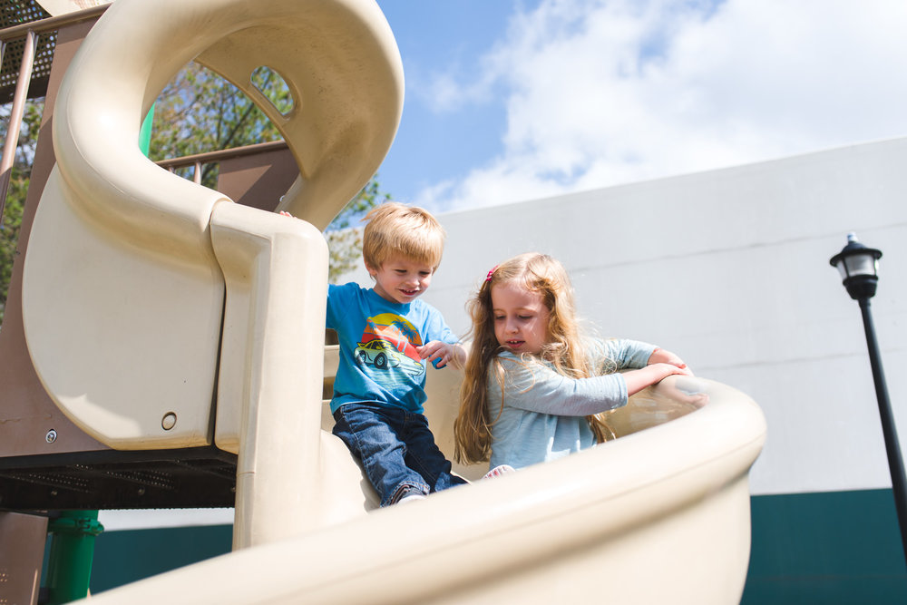 Little boy and girl going down a playground slide.