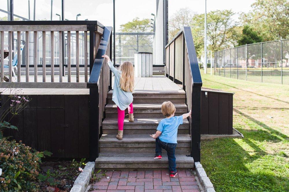 Kids walking up steps at tennis courts.