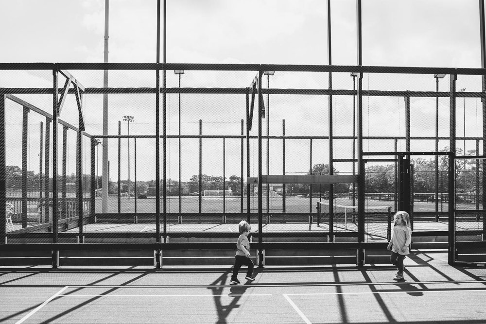Kids playing on tennis court.