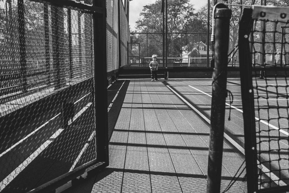 Little boy on tennis court.
