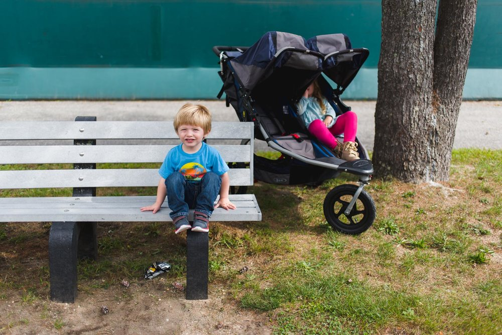 Little boy sitting on park bench with sister in stroller.
