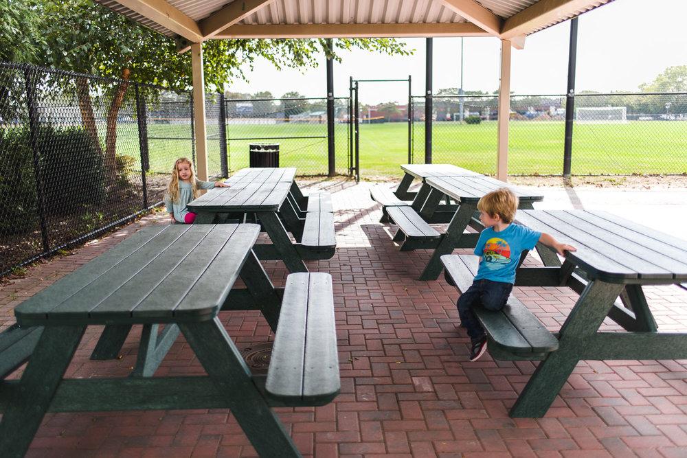 Boy and girl play at picnic tables.