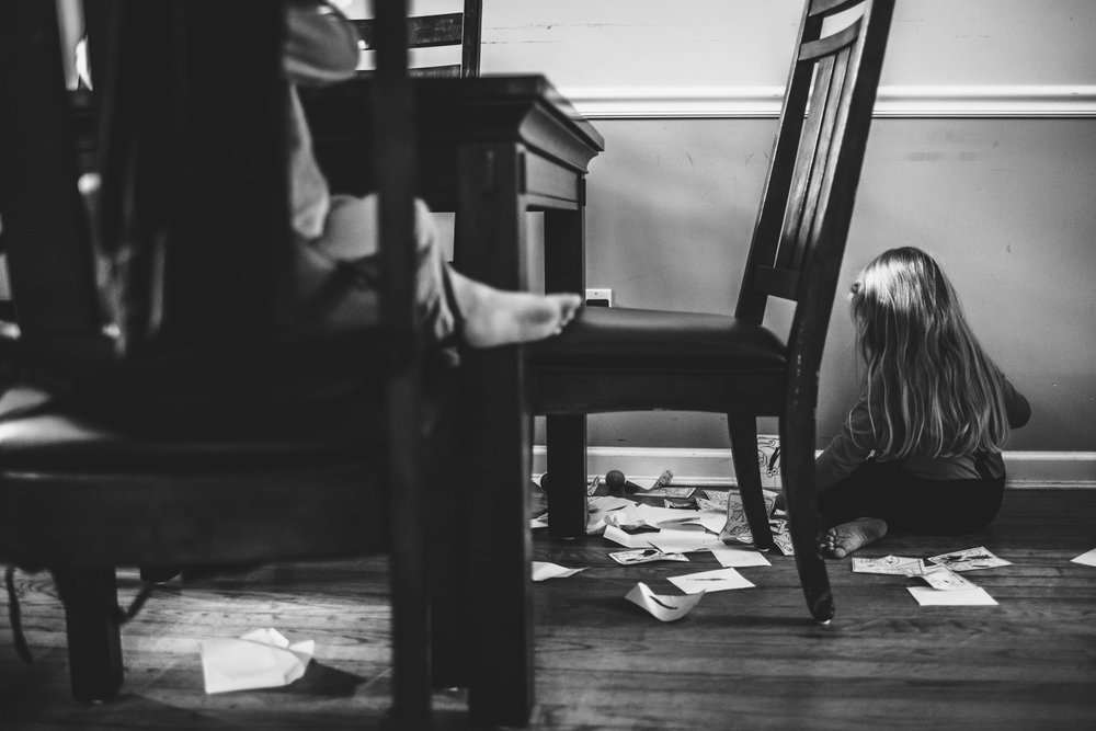 Little girl sitting on floor amidst a stack of papers.