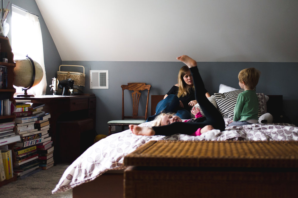 Mother and kids playing on bed.