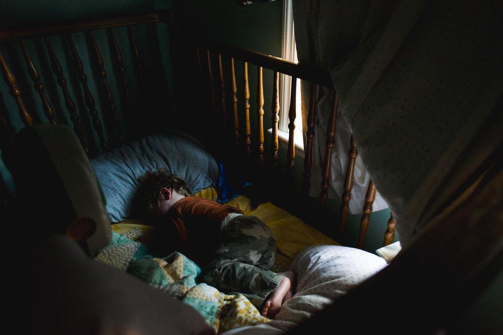 Little boy taking a nap in crib.