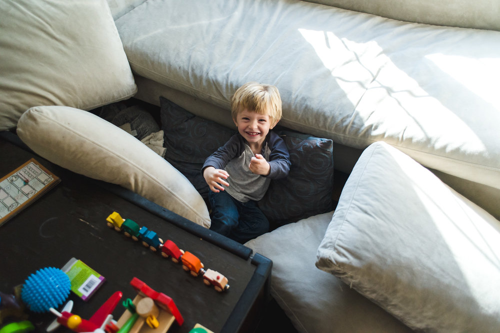 Little boy laughing amidst a pile of pillows