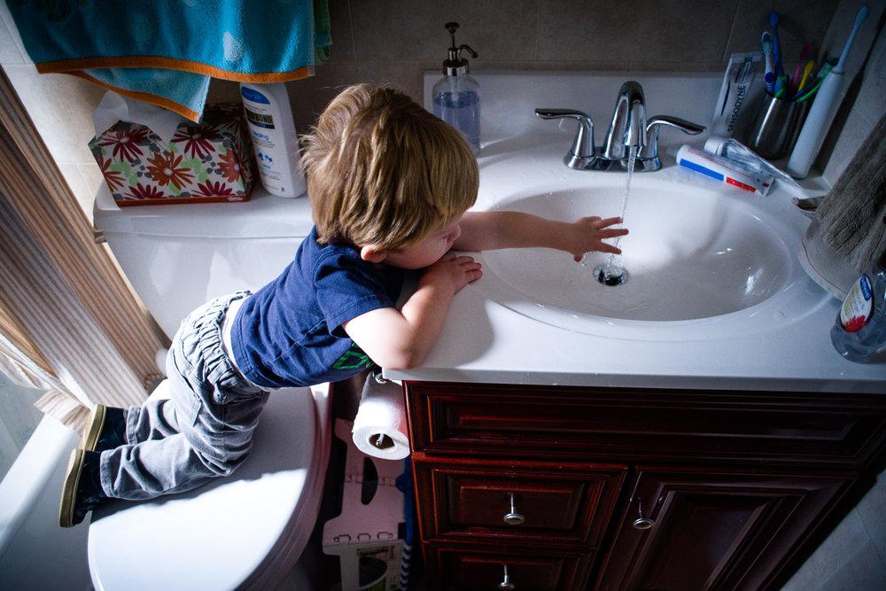 Little boy playing in bathroom sink.