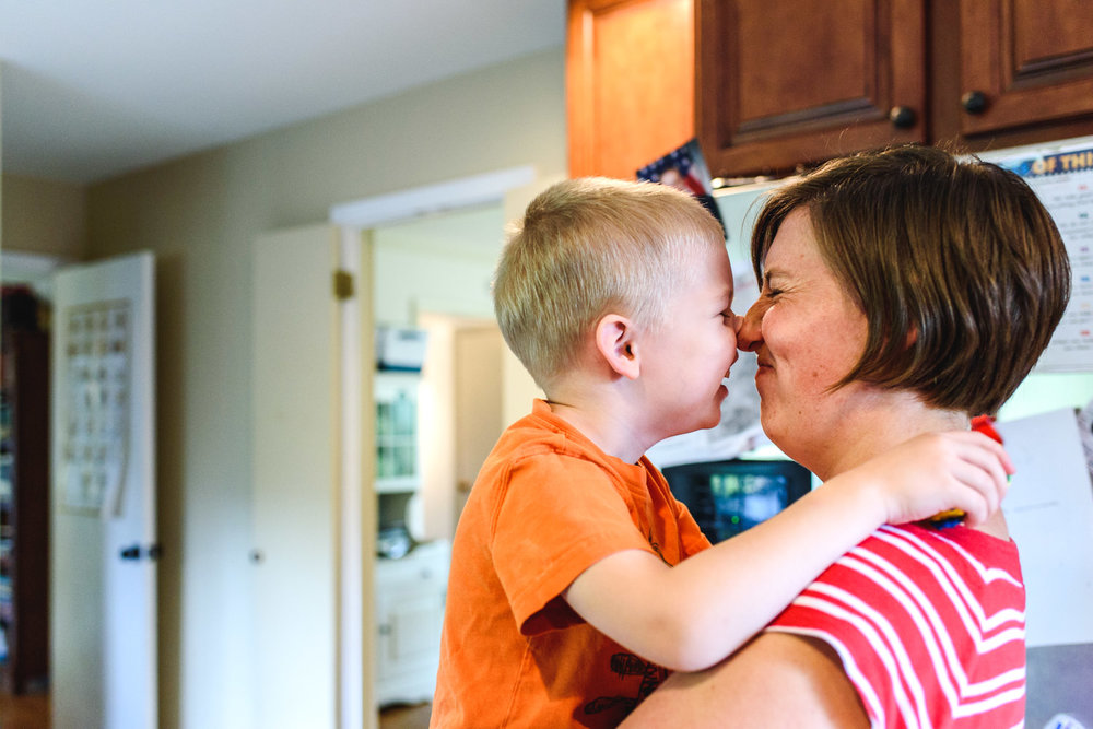Mother and son rubbing noses in kitchen.