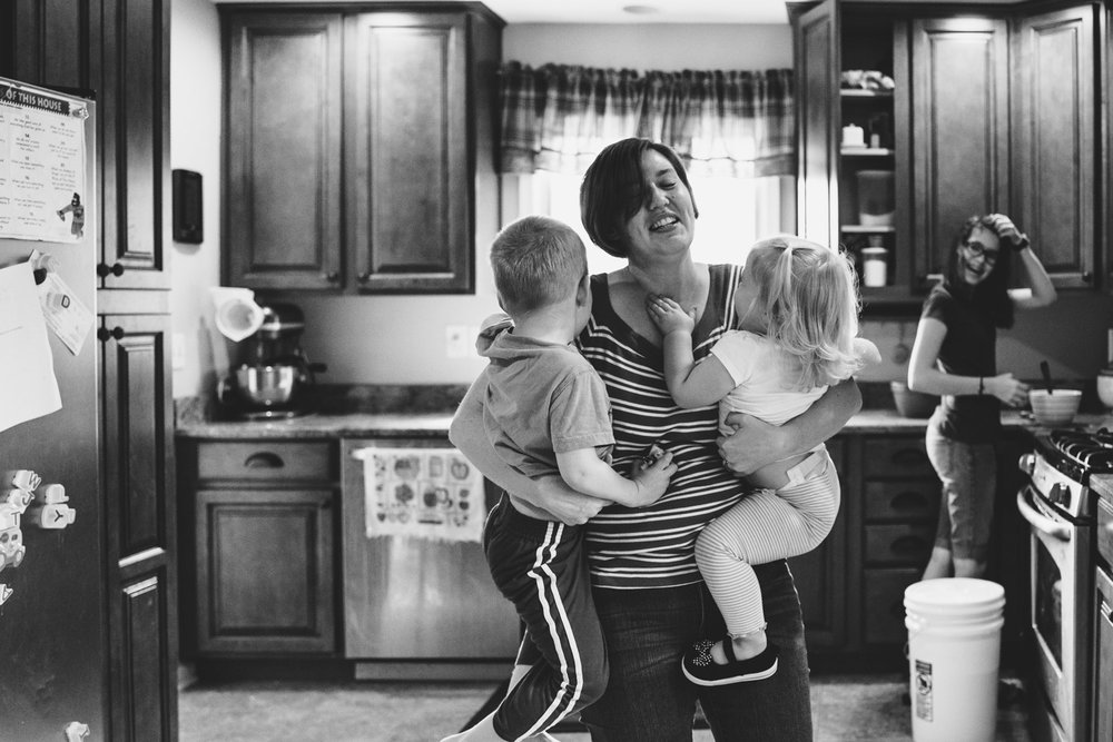 Mother carrying two toddlers in the kitchen.