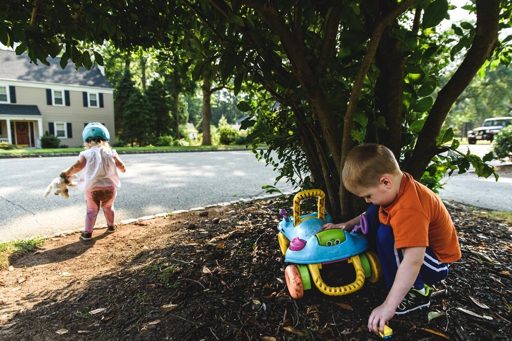 Kids playing in the dirt in the front yard.