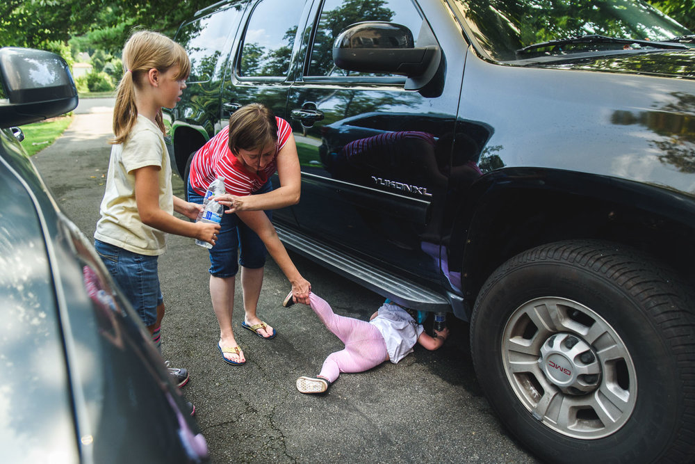 Mother pulling toddler out from under a car.
