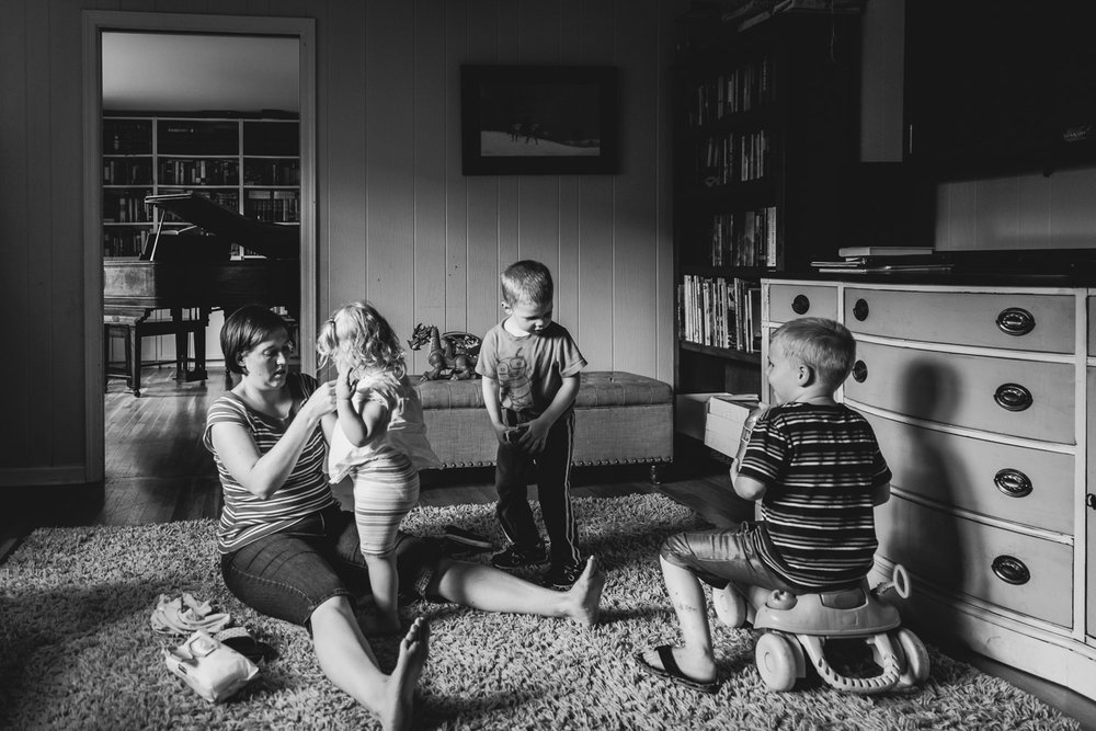 Mother changing toddler's clothes with brothers looking on.
