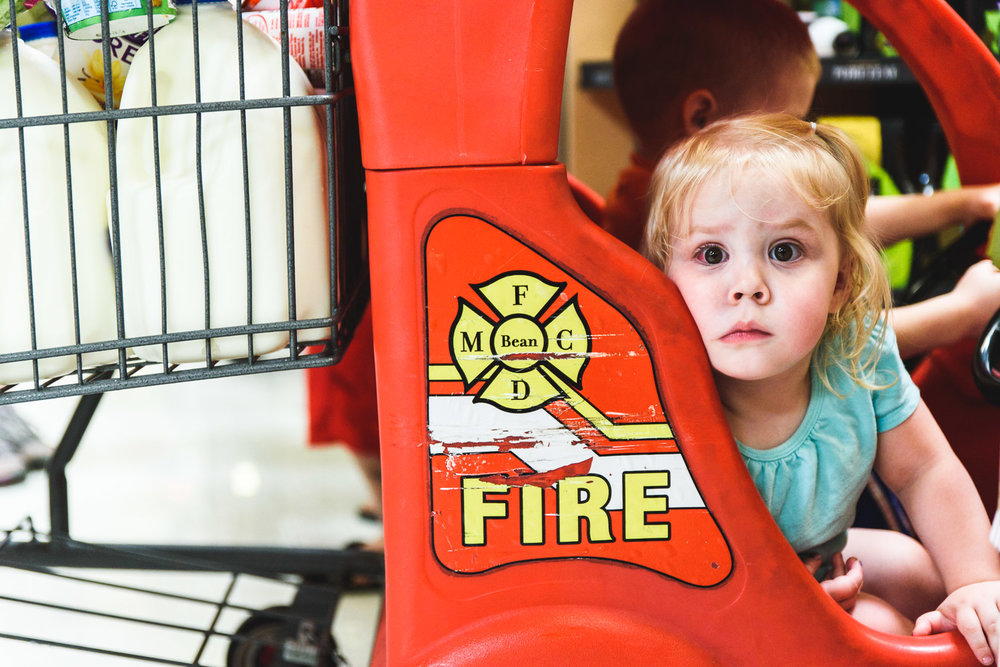 Little girl wide-eyed in shopping cart.
