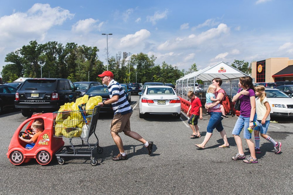 Family of eight walking through grocery store parking lot.