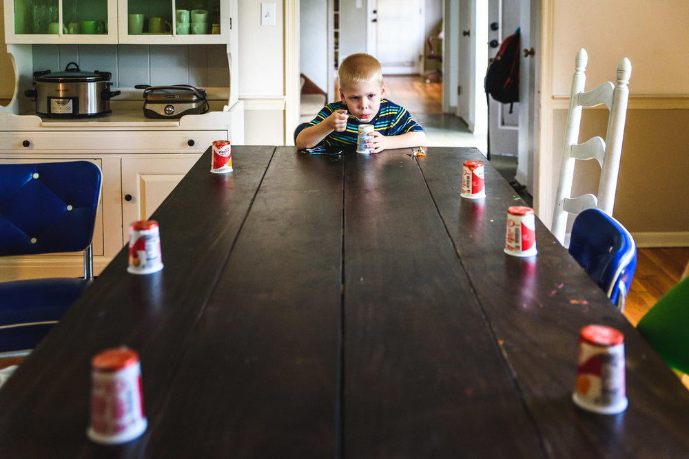 Little boy eating a yogurt.