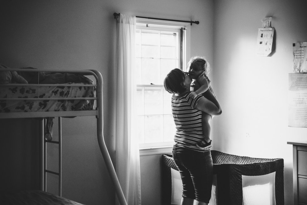 Mother picking up toddler daughter from nap.