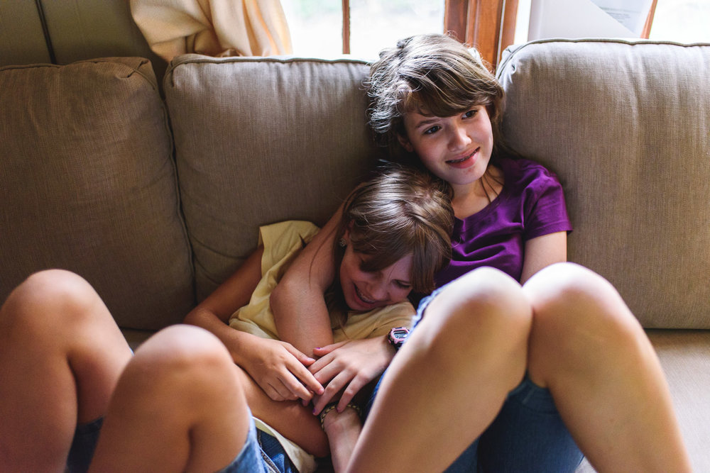 Teenage sisters cuddling on the couch.