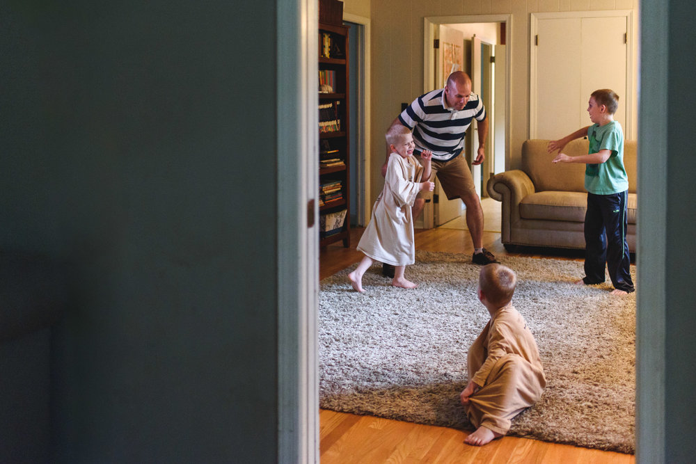 Father wrestling with his little boys.