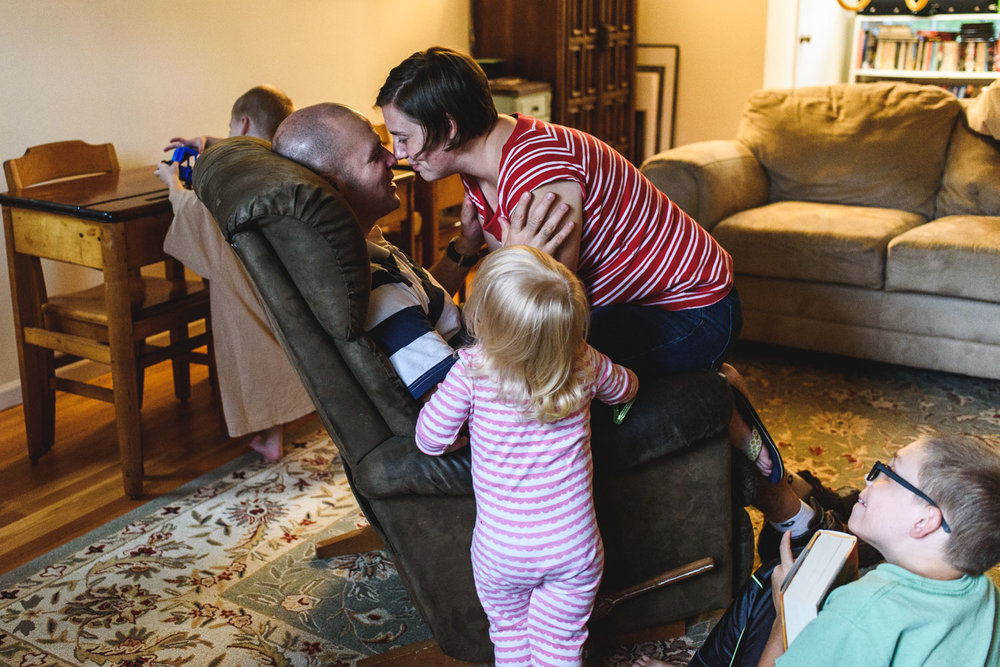 Parents embracing with children looking on.
