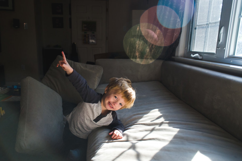 Little boy leaning on couch with sun flare.