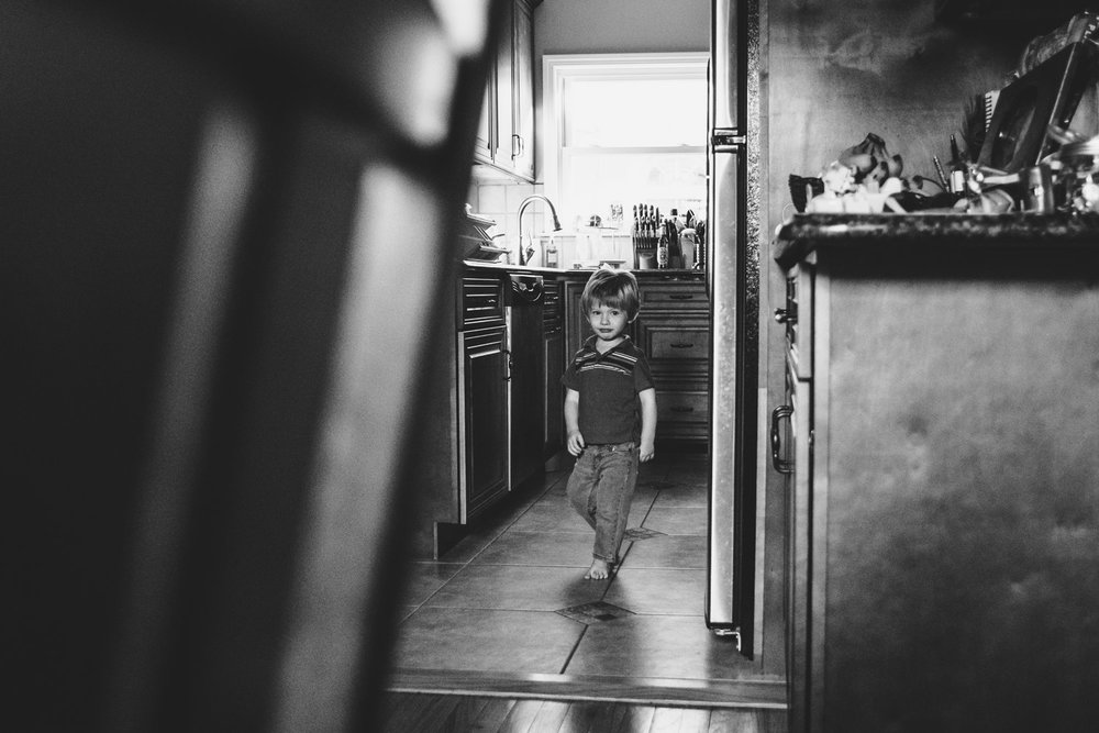 Little boy walking through the kitchen.