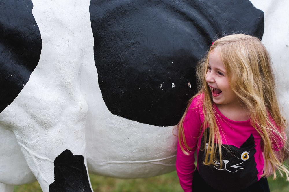 Girl laughing next to fake cow.