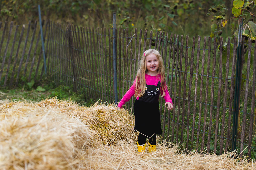 Little girl walking through the hay.