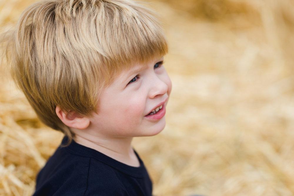 Portrait of little boy in hay.