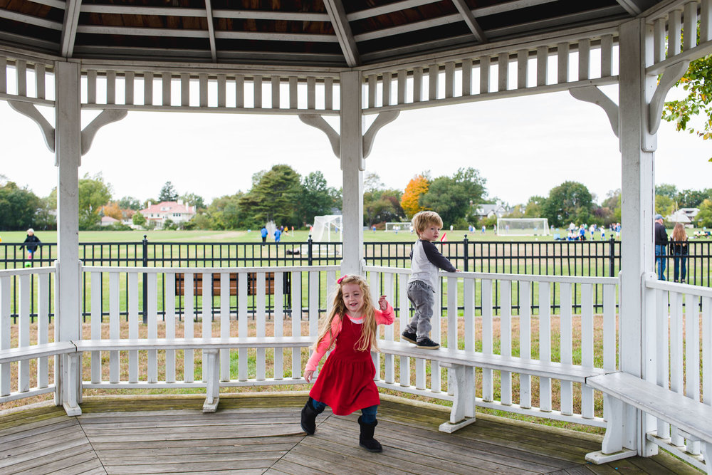 Boy and girl playing in a gazebo.