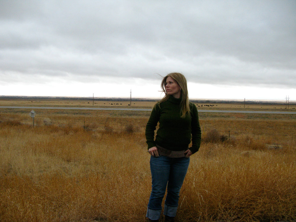 Woman standing in field on cloudy day.