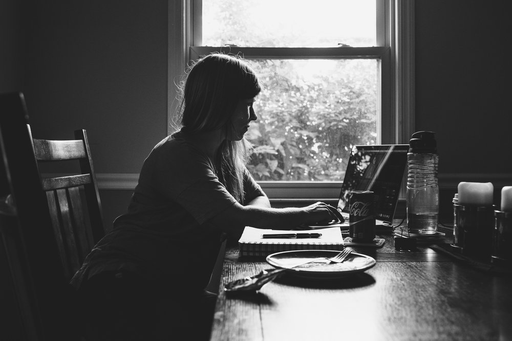 Woman working on computer at kitchen table.