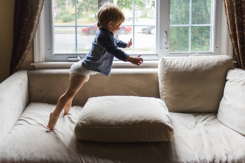 Little boy in diaper jumping on the couch.