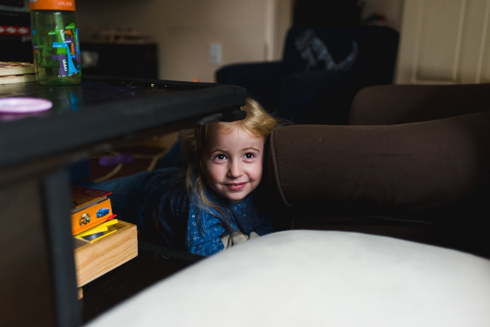 Little girl hiding under coffee table.