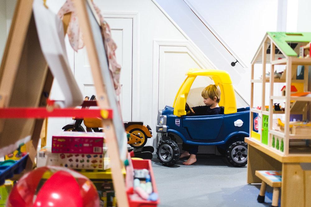 Little boy sitting in toy car in playroom.