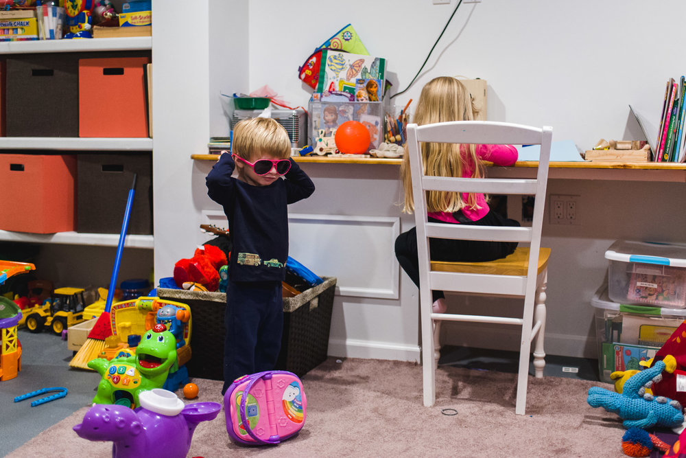 Little boy in sunglasses playing in playroom while sister draws at her desk.