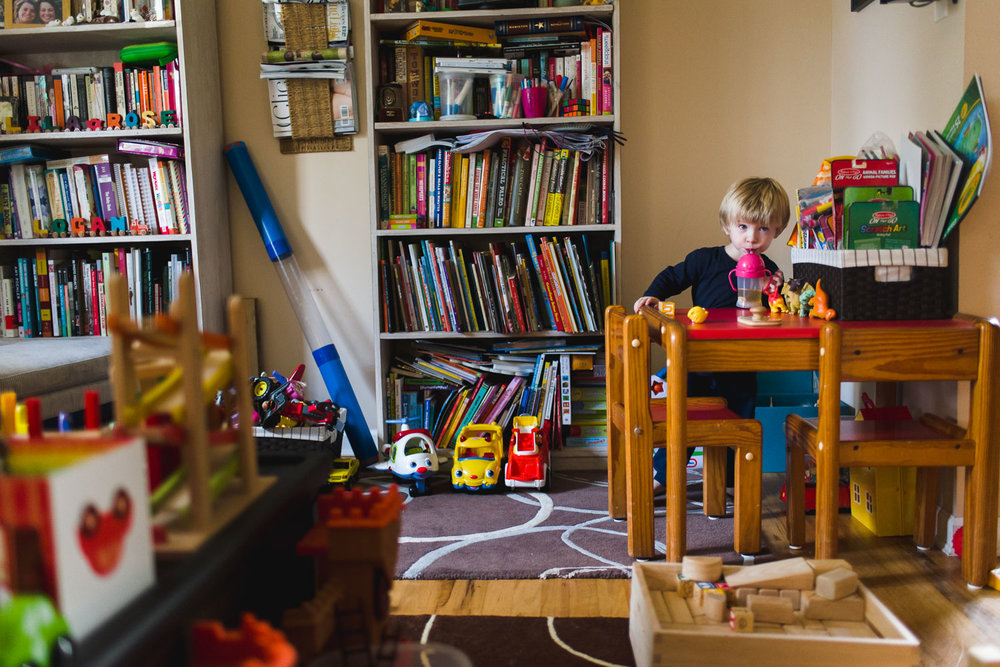 Little boy playing with toys in living room.