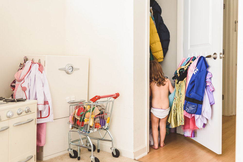 Little girl in underwear looking through clothes in closet.