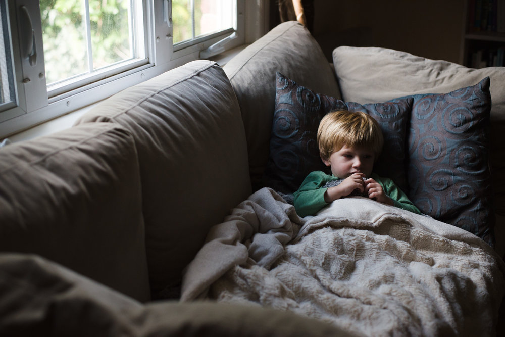 Toddler boy resting under a blanket on the couch.