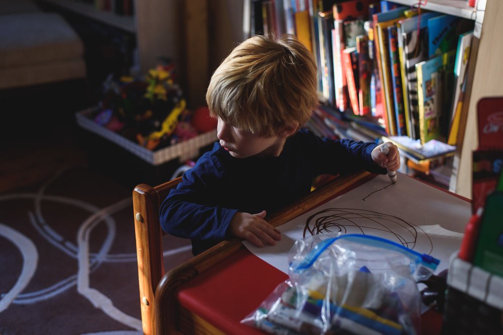 Little boy coloring in the living room.
