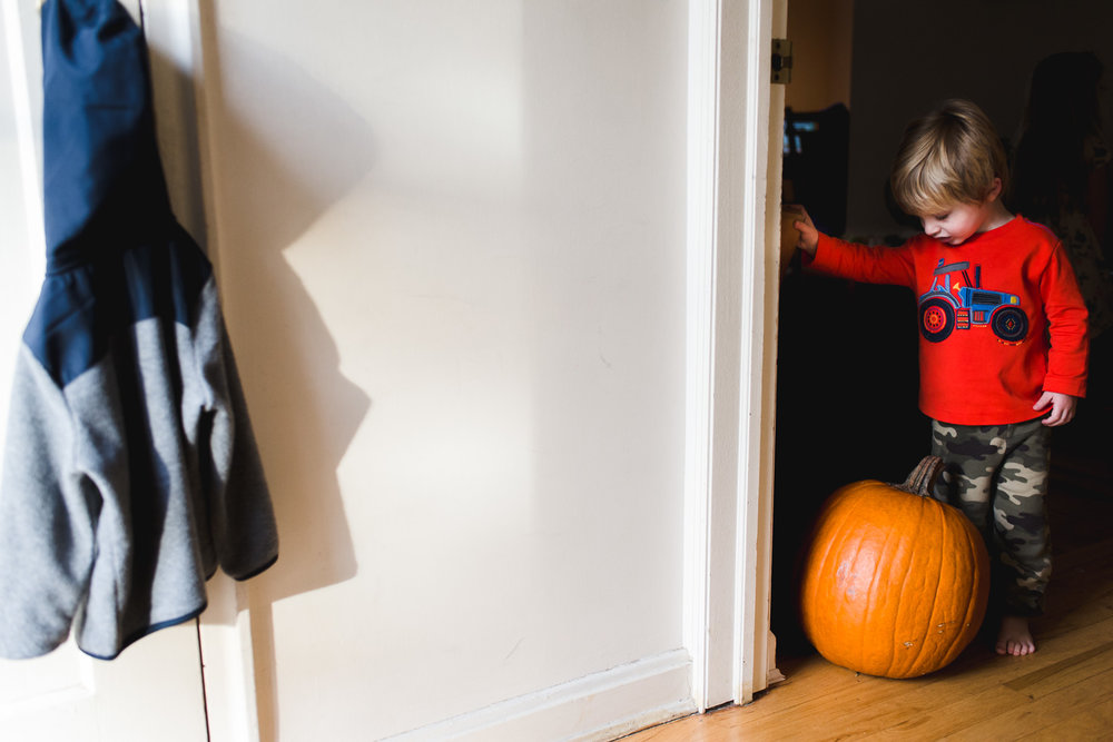 Boy in hallway with pumpkin.