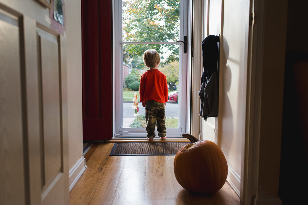 Boy looking out front door with pumpkin behind him in the hallway.