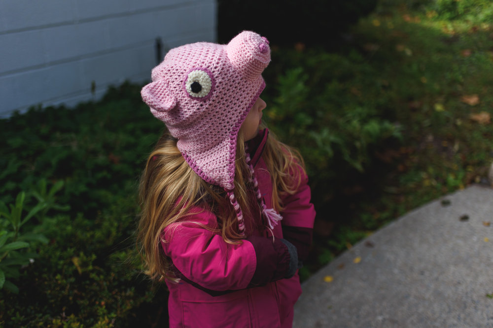 Little girl in Peppa Pig hat.