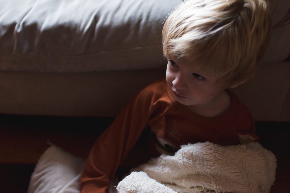Portrait of little boy with fuzzy blanket.